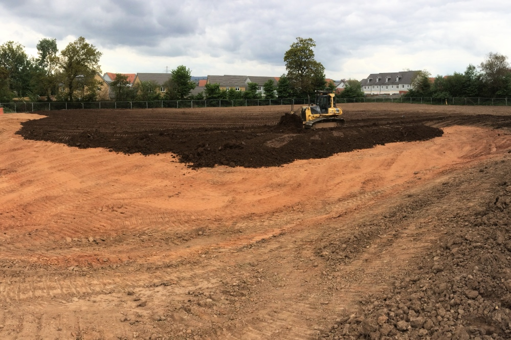 Spread topsoil for new playing field
